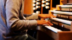 a visitor plays the church organ